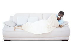 Sick man lying on couch blowing his nose Royalty Free Stock Image