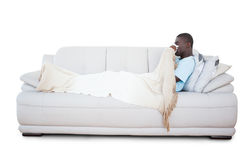 Sick man lying on couch blowing his nose Stock Photos