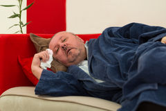 Sick man lying down on couch with high fever Stock Photos