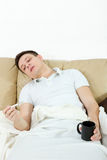 Sick man lying on sofa measuring temperature with thermometer Stock Images