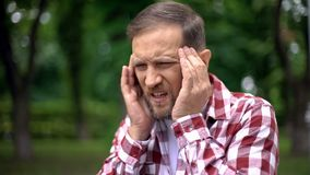 Sick man massaging temples, suffering from migraine, sharp pain, neurology. Stock photo stock images