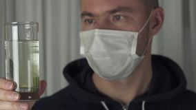 Sick man in medical mask dissolves the effervescent tablet in a glass of water slow motion stock footage video stock video