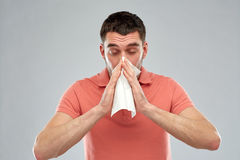 Sick man with paper napkin blowing nose Royalty Free Stock Photography