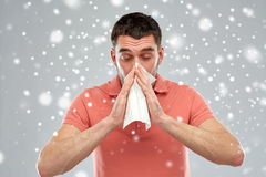 Sick man with paper wipe blowing nose over snow Royalty Free Stock Photo