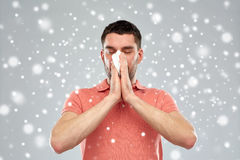 Sick man with paper wipe blowing nose over snow Stock Photography