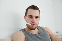 Sick man posing with thermometer Royalty Free Stock Image