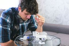 Sick man pours the saline from the syringe into the container for the inhaler. royalty free stock photography