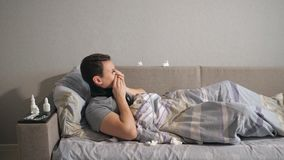 Coughing man lying on sofa. Sick man in scarf lying under warm blanket on comfortable couch at home stock footage