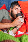Sick Man Sipping on Tea. A sick man sipping tea from a mug, on the couch, wrapped in a blanket with tissue paper all around Royalty Free Stock Photos