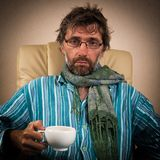 Sick man sitting in chair with cup. Mature sick man sitting in chair with cup Stock Photo