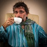 Sick man sitting in chair with cup. Mature sick man sitting in chair with cup Royalty Free Stock Photo