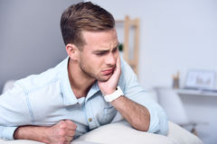 Sick man sitting on the couch Royalty Free Stock Photo
