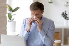 Sick man sitting at office and sneeze running nose. royalty free stock image