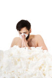 Sick man sneezing into handkerchief. Stock Photography