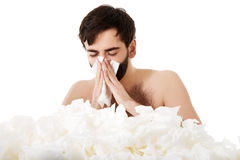 Sick man sneezing into handkerchief. Stock Photo