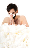 Sick man sneezing into handkerchief. Royalty Free Stock Images