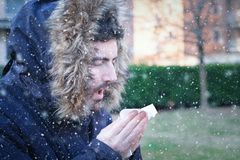 Sick man sneezing in the kleenex in winter. Sick man sneezing in the handkerchief during cold season Royalty Free Stock Image