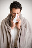 Sick Man Sneezing. Pale sick man with a flu, sneezing, in a clean background Royalty Free Stock Photos
