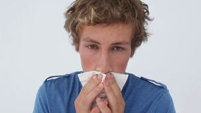 Sick man sneezing into a tissue Stock Image