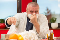 Sick man suffering cold and winter flu virus drinking tea royalty free stock photos