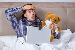 The sick man suffering from flu in the bed. Sick man suffering from flu in the bed Stock Images