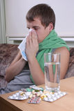 Sick man with tablets ans glass of water Stock Images