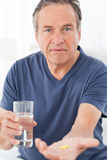 Sick man taking his pills Stock Photo