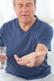 Sick man taking his pills Stock Image