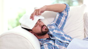 Sick man taking his temperature on the couch