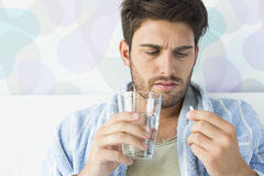 Sick man taking medicine in bedroom at home Stock Photo