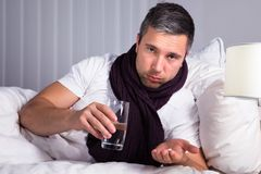 Sick man taking medicines Stock Photo