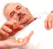 Sick man taking pills. Elderly man laying in bed taking pills - focus on eyes Royalty Free Stock Photo