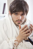 Sick man with tea. Portrait of sick man in bed holding a cup warm tea royalty free stock photo