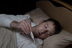 Sick Man testing his temperature Stock Photo
