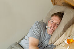 Sick Man testing his temperature with thermometer. Horizontal photo of mature man with thermometer in mouth while lying in bed Stock Photo