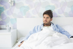Sick man with thermometer in mouth reclining on bed at home Stock Photography