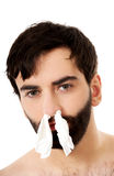 Sick man with tissues in nose. Royalty Free Stock Photography