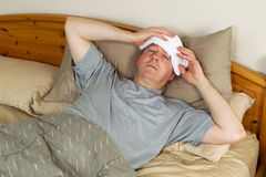 Sick Man Treating Fever. Horizontal photo of mature man treating fever by holding wash cloth to his forehead while lying in bed Stock Photos