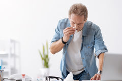 Sick man using his computer. Work with me. Office worker wearing casual clothes wiping his nose while standing behind workplace stock photo