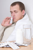 Sick man using nasal spray in living room Stock Photo