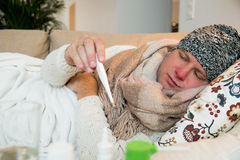 Sick man wearing scarf lying on couch Royalty Free Stock Image