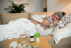 Sick man wearing scarf lying on couch Stock Image