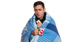 Sick man wrapped in a blanket holding a tea cup Royalty Free Stock Photography