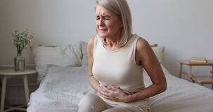 Sick mature woman hold belly feel abdominal ache in bed
