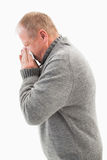 Sick mature man blowing his nose Stock Images