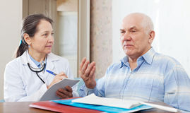 Sick mature man complaining  to doctor about symptoms Royalty Free Stock Photo