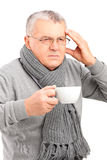 Sick mature man holding a cup of tea and gesturing headache Royalty Free Stock Image