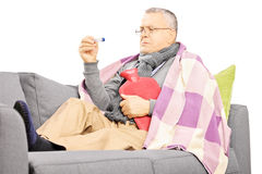 Sick mature man on a sofa with a hot-water bottle looking at the stock image