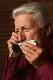 Sick mature man speaking on phone Royalty Free Stock Image