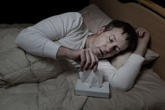 Sick mature man using tissue while in bed Stock Images